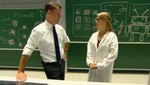 Eine Frau im weißen Kittel und ein Mann im Anzug befinden sich vor einer Tafel und sprechen miteinander.