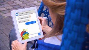 Ein Display, auf dem ein Chatverlauf zu sehen ist sowie in der Ecke unten links eine Raupe mit blauen Haaren und rotem Käppi.