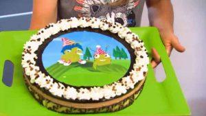 Auf einem grünen Tablett befindet sich eine runde Torte, auf der eine Raupe mit blauen Haaren und eine grüne Laus mit Gesicht gedruckt ist.