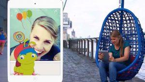 Eine Frau mit T-Shirt sitzt in einem blauen Hängekorb auf einem Bürgersteig. Links im Bild ist ein Handydisplay eingeblendet, auf dem sich eine lachende Frau und eine Raupe mit blauen Haaren und roten Käppi befindet.