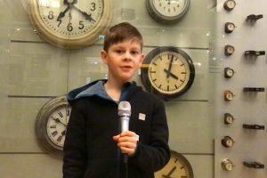 Ein Junge mit blonden Haaren steht vor einer Wand, an der viele Uhren hängen.