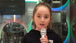 Ein Mädchen mit dunklen Haaren und Zopf spricht in ein Mikrofon.