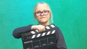 Ein Mädchen mit blonden Haaren und Brille hält eine Filmklappe in der Hand.