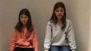 Zwei Mädchen sitzen nebeneinander vor einer weißen Wand.