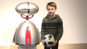 Ein Junge steht neben einem Roboter und hält einen Fußball in den Händen.
