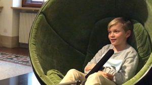 Eine Junge mit blonden Haaren sitzt in einem grünen Ohrensessel und spricht in ein Mikrofon.