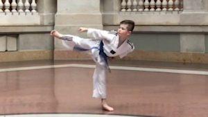 Ein Junge im Taekwon-Do-Anzug führt einen Kampfschritt aus.