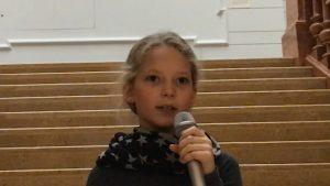 Ein Mädchen mit blonden Haaren steht auf einer Treppe und spricht in ein Mikrofon.