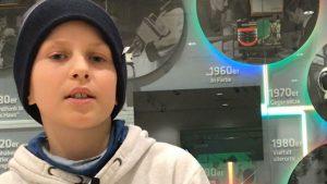 Ein Junge mit schwarzer Mütze spricht in die Kamera.