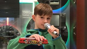 Ein Junge mit kurzen braunen Haaren hält eine Lokomotive in die Kamera.