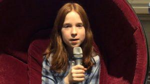 Ein Mädchen mit roten Haaren sitzt in einem Ohrensessel und spricht in ein Mikrofon.
