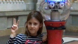Ein Mädchen mit gestreiften Shirt steht neben einem Roboter.