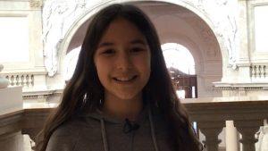 Ein Mädchen mit langen dunkelbraunen Haaren lacht in die Kamera.