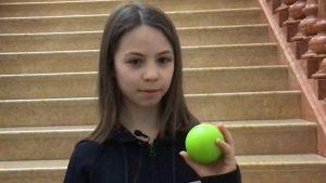 Ein Mädchen mit hellbraunen Haaren hält einen Hockeyball in die Kamera.