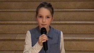 Ein Mädchen mit einem Zopf spricht ins Mikrofon.