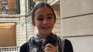 Ein Mädchen mit einem Halstuch spricht ins Mikrofon.