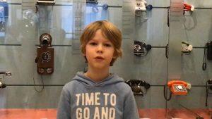 Ein Junge mit hellblauen Pullover steht vor einem Glaskasten, in denen Telefone hängen.