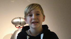 Ein Junge mit blonden Haaren und Seitenscheitel lacht in die Kamera.
