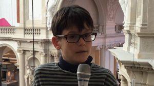 Ein Junge mit Brille und braunen Haaren spricht in ein Mikrofon.
