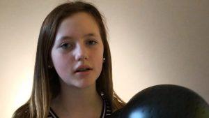 Ein Mädchen mit langen braunen Haaren hält einen Reithelm in der Hand.