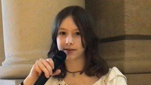Ein Mädchen mit dunklen, schulterlangen Haaren spricht in ein Mikrofon.